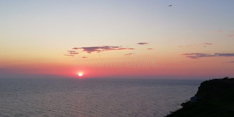 Wolken und Schattenbilder von Vögeln gegen den Hintergrund des Seesonnenuntergangs in den blauen, roten und rosa Farben lizenzfreie stockfotografie