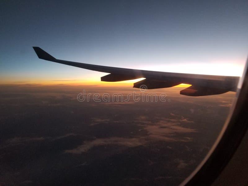 Wolken und Sonnenuntergang-umgebender Flugzeug-Flügel lizenzfreie stockbilder