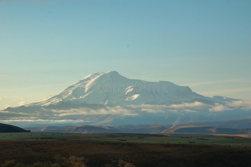 Wolken wickelten oben einen riesigen Hügel ein und ihr Morgen war warm stockbilder