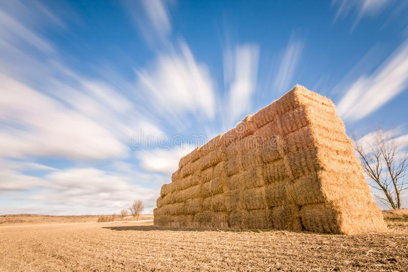 Clouds move over fields and straw bales stock photography