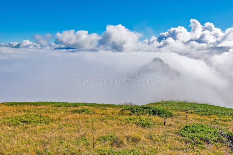 Wolkenabdeckungsberg übersteigt zur Herbsttageszeit lizenzfreie stockfotos