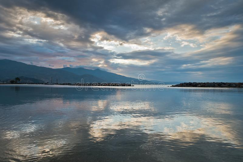 Wolkenbezinningen in een water van Egeïsche overzees bij zonsopgang, Volos-haven met Pelion-berg op achtergrond stock foto's