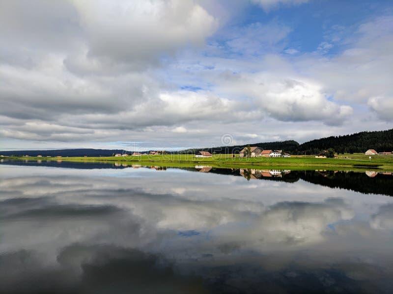 Wolkenbezinningen over Lac des Thaillère, Zwitserland royalty-vrije stock afbeelding