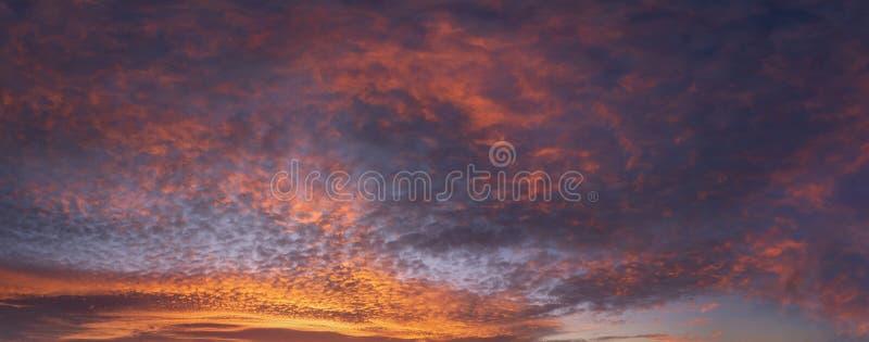 Wolkendecke bei Sonnenuntergang mit roten Wolken am Himmel lizenzfreie stockbilder