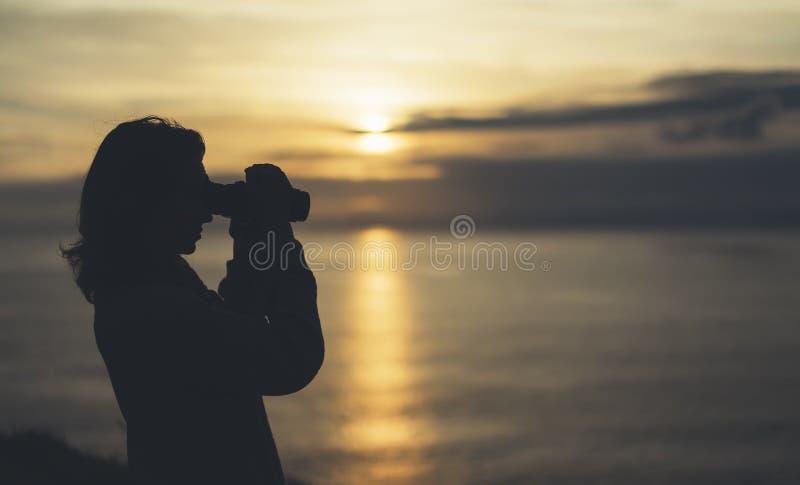 Wolkenhemel en zonlichtzonsondergang op horizonoceaan De fotograaf die van de de toeristenreiziger van de silhouetpersoon beelden royalty-vrije stock foto