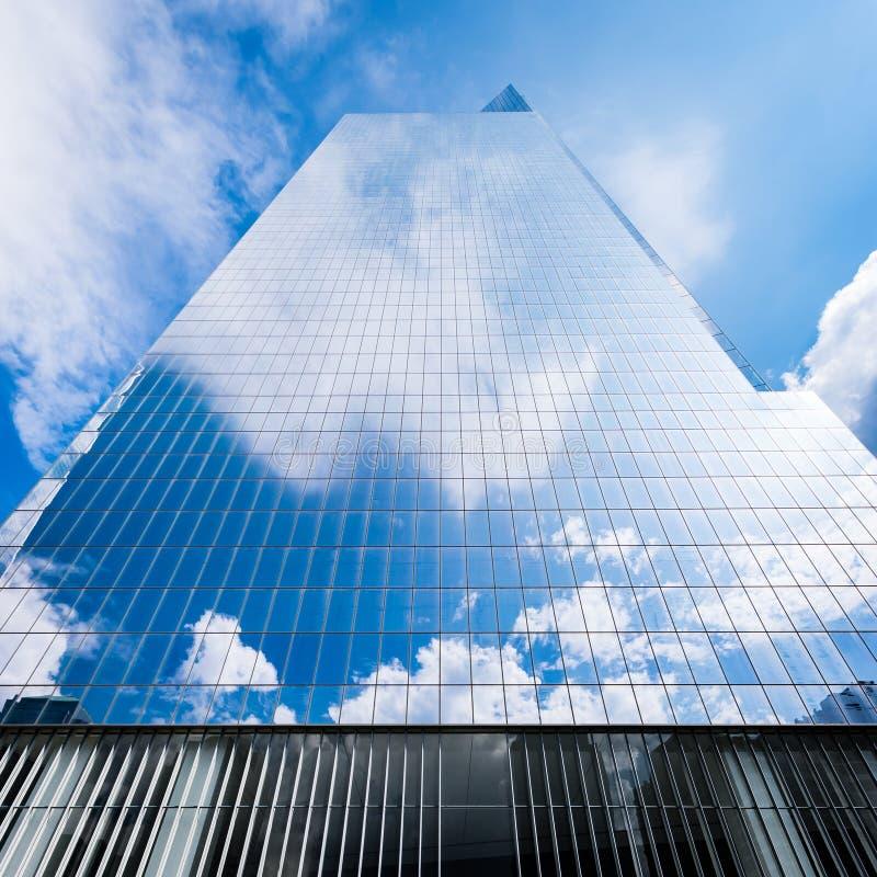 Wolkenkrabber die op blauwe hemel en witte wolken wijzen royalty-vrije stock foto's