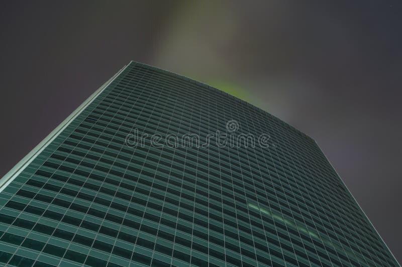 Wolkenkrabber in mist met gloeiende vensters bij nacht stock foto