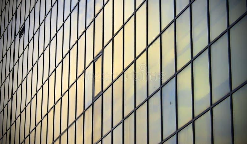 Wolkenkrabber van de de bouwvensters en hemel bezinning in vensters royalty-vrije stock foto