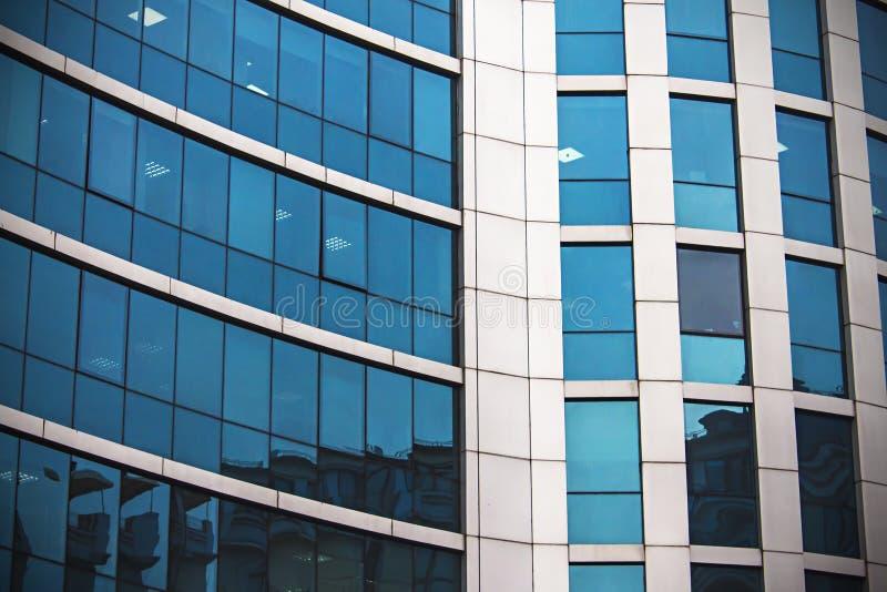 Wolkenkrabber van de de bouwvensters en hemel bezinning in vensters royalty-vrije stock fotografie