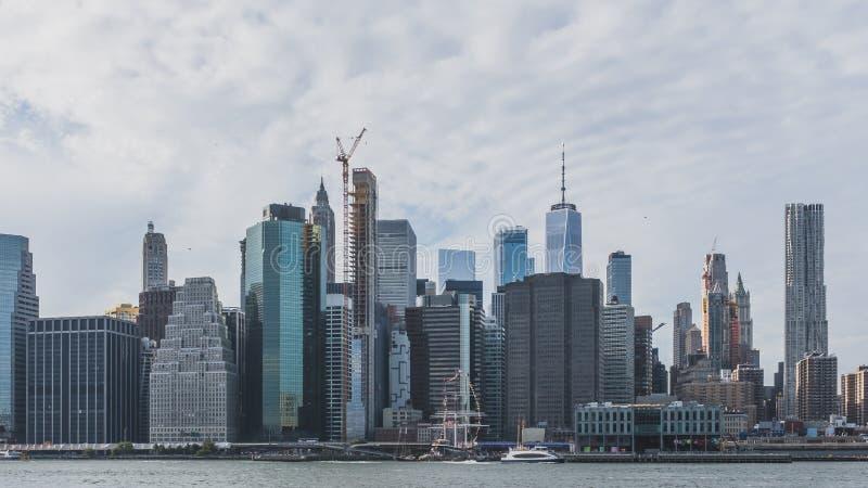 Wolkenkrabbers van Manhattan van de binnenstad die over de Rivier van het Oosten, van de Brugpark van Brooklyn worden bekeken, in stock foto