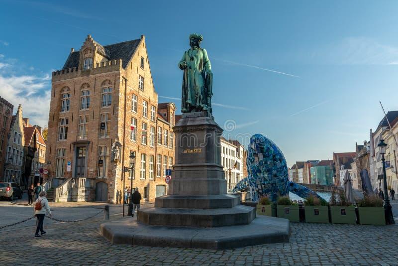 Wolkenkratzer, der Brügge-Wal und Statue von Van Eyck stockfotos