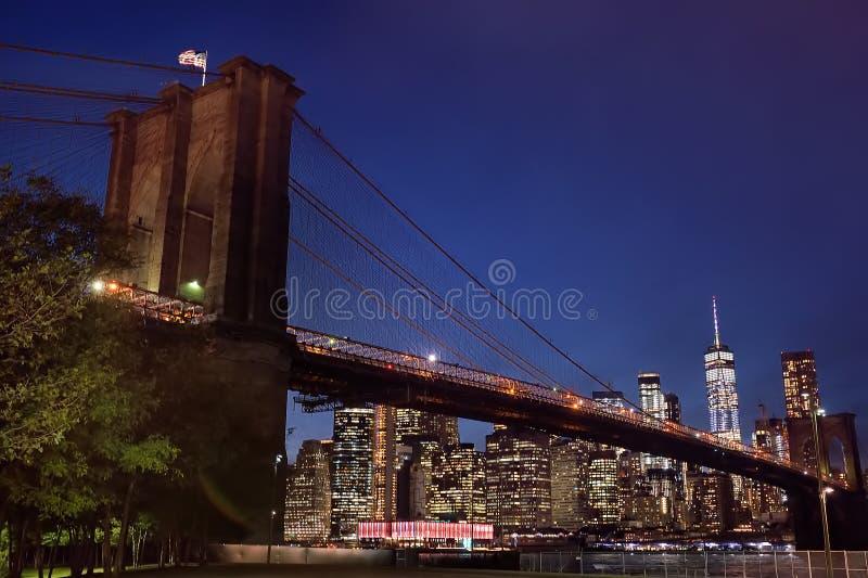 Wolkenkratzer von Manhattan und von Brooklyn-Brücke an der Dämmerung stockfotografie