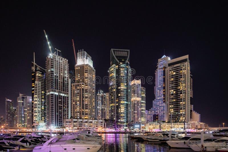 Wolkenkratzer zeichnen den Jachthafen in Dubai nachts stockfotografie