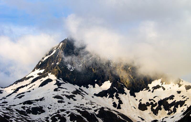 Wolkenpas door een Bovenkant van de Sneeuwberg royalty-vrije stock afbeelding