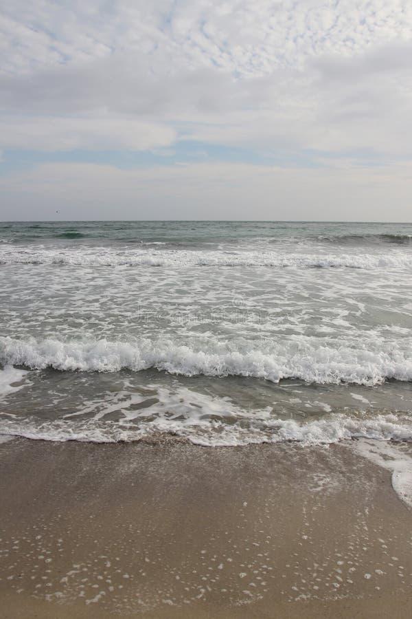 Wolkiges Wetter Goldener Sand, Wellen und Schaum Bewölkter Tag auf dem sandigen Strand Panoramablick des schönen sandigen Strande stockfotografie