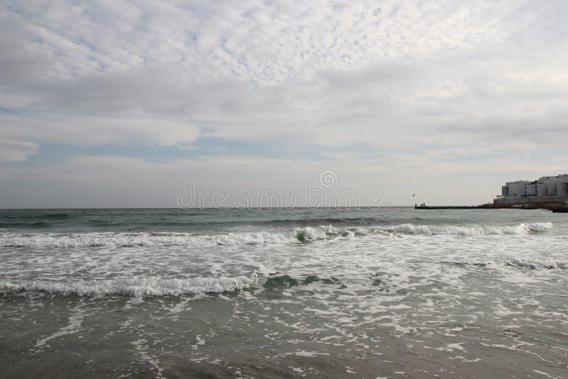 Wolkiges Wetter Goldener Sand, Wellen und Schaum Bewölkter Tag auf dem sandigen Strand Panoramablick des schönen sandigen Strande stockbilder