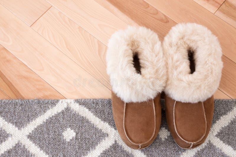 Wolldecke und Pantoffel auf Bretterboden lizenzfreie stockbilder
