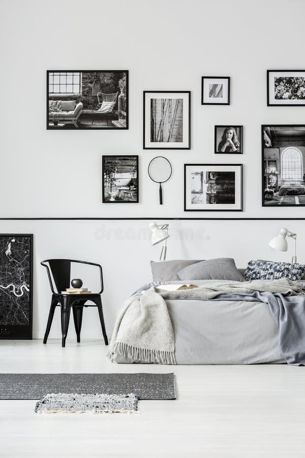 Wolldecken und Stuhl nahe bei Bett im weißen Schlafzimmerinnenraum mit Galerie von Plakaten Reales Foto lizenzfreie stockbilder
