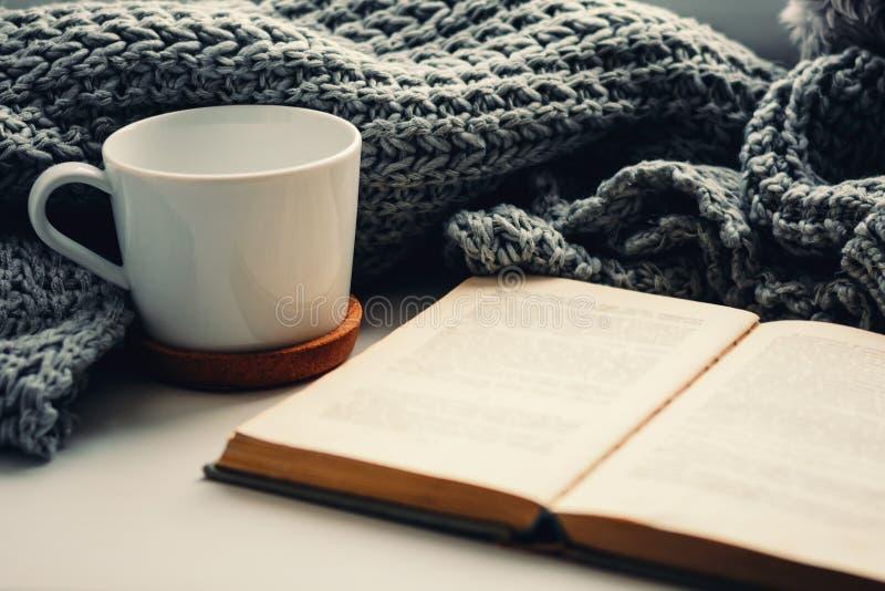 Wollen sjaal, een kop thee en een boek op de vensterbank Hygge en comfortabel de herfstconcept stock afbeeldingen