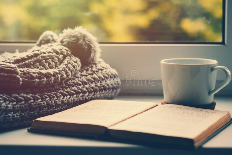 Wollen sjaal, een kop thee en een boek op de vensterbank Hygge en comfortabel de herfstconcept stock foto's