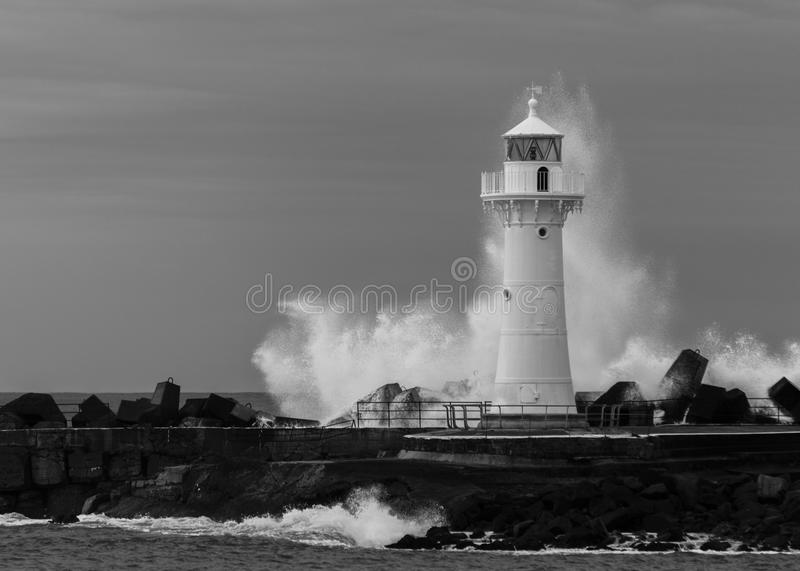 Wollongong Breakwater Lighthouse. Black and white photo of waves breaking at Wollongong Breakwater Lighthouse in Wollongong Harbour, south of Sydney, New South royalty free stock image