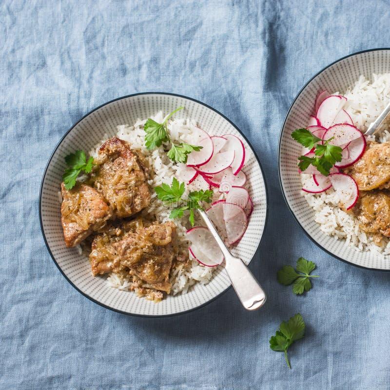 Wolna kuchenki wieprzowina z ryżową pilaf i rzodkwi sałatką na błękitnym tle fotografia stock