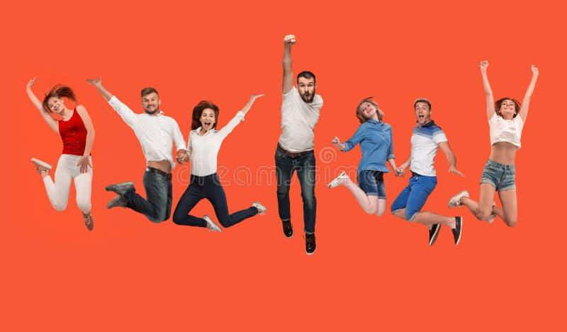 Wolność w chodzeniu młody człowiek i kobiety skacze przeciw czerwonemu tłu obrazy royalty free