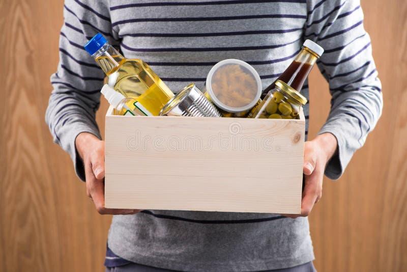 Wolontariusz z darowizny pudełkiem z żywność na drewnianym tle obraz stock