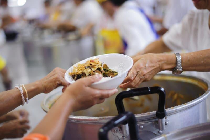 Wolontariuszi dają jedzeniu bezdomna bieda: pojęcie humanitarny zdjęcia royalty free
