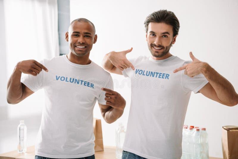 Wolontariuszi wskazuje przy znakami na koszulkach zdjęcie royalty free