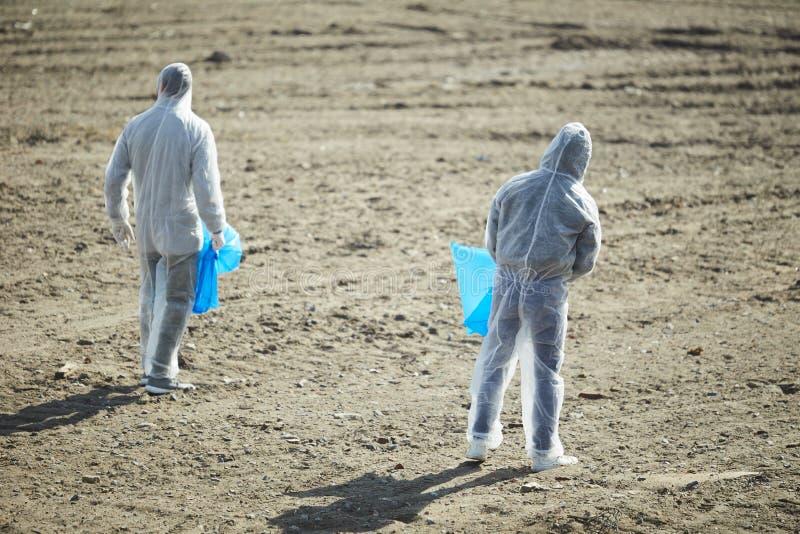 Wolontariuszi z torbami w ochrona kostiumach zdjęcie royalty free