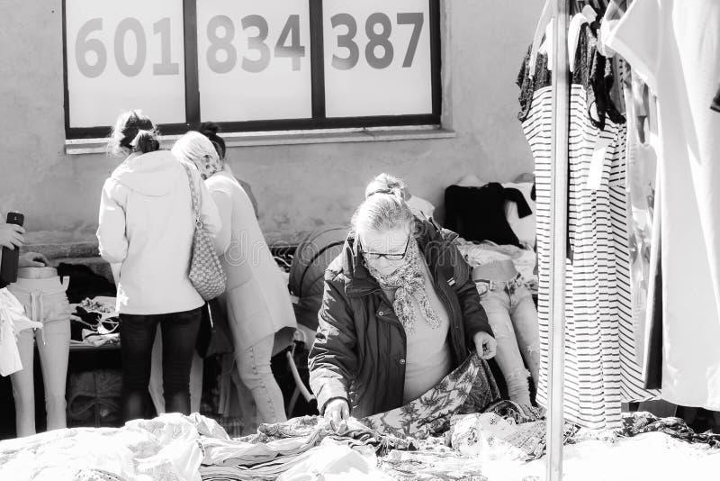 WOLSZTYN, POLONIA - 21 DE ABRIL DE 2016 Una mujer que examina la ropa en la exhibición en el soporte local del mercado imagenes de archivo