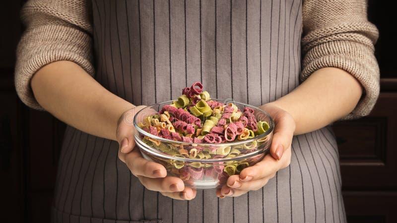Womal tenant le bol en verre avec les pâtes colorées sèches photo stock