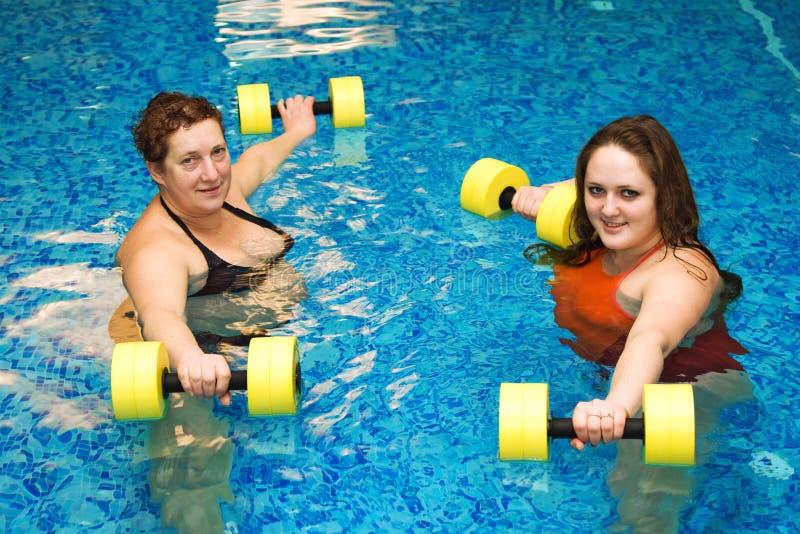 Womam dos en agua con pesas de gimnasia fotos de archivo