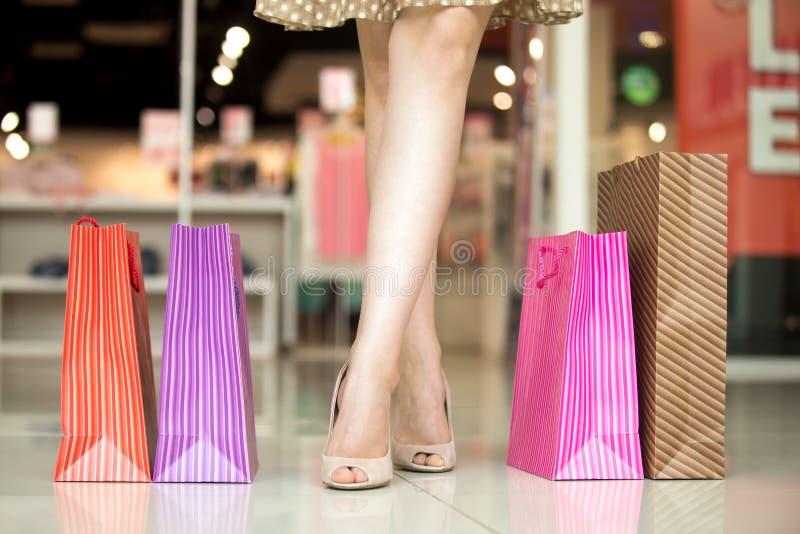 woman's腿特写镜头站立在与袋子的购物中心的 库存照片
