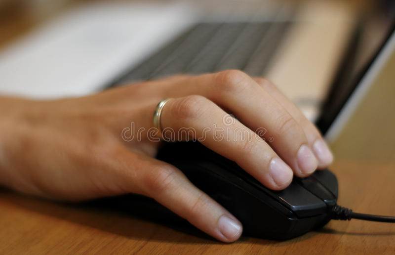 Woman's hand on the computer mouse at the work place stock photo