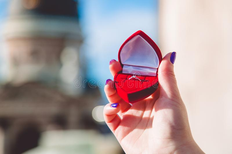 Woman's hand is holding engagement ring with diamond in the red box of heart form in front of architecture blur background stock photos