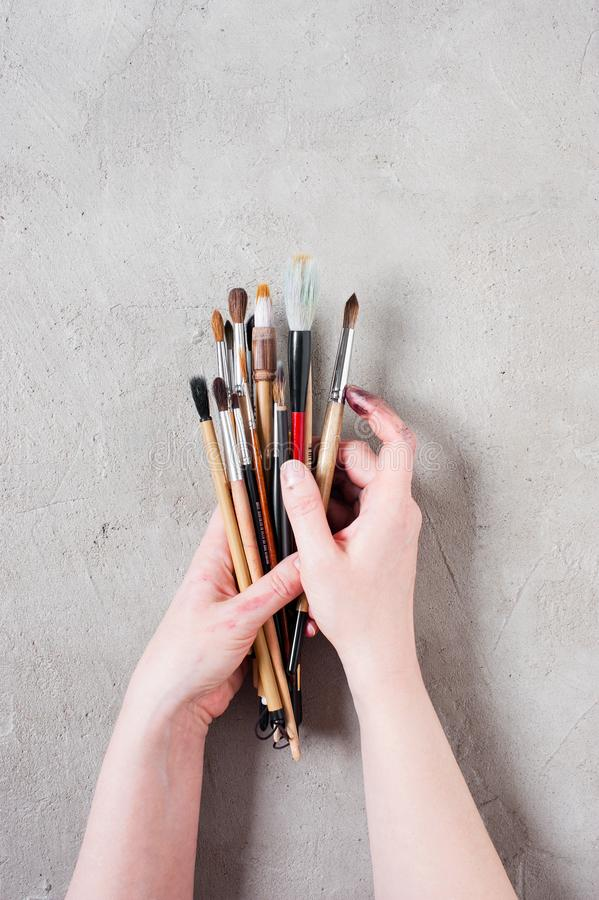 Woman's hands holding the bunch of art brushes. On the textured grey table, top view royalty free stock photos