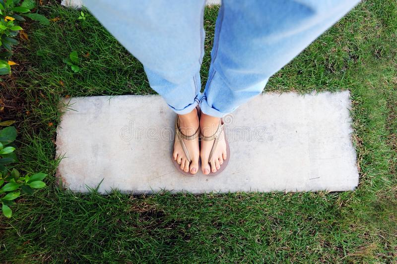 Close Up Woman's Legs and Feet Wearing Flip Flops on the Green Grass Background. Woman's Legs and Feet Wear Gold Sandals on Cement and Green Grass royalty free stock photo