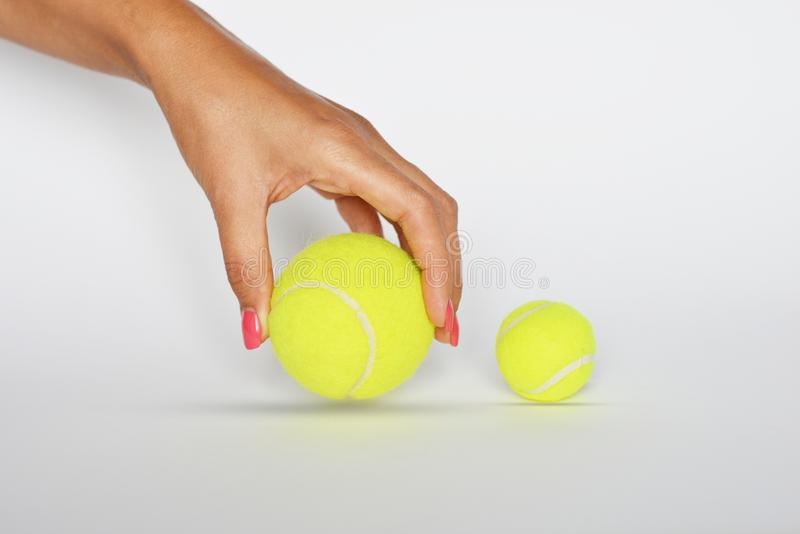 Woman's ręka wybiera dużą tenisową piłkę na białym tle zdjęcia royalty free