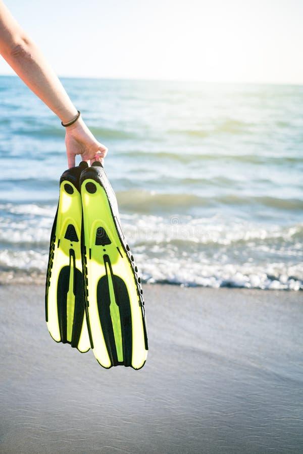 WomanÂs fena för snorkel och för simning för handuppehälle på en sandig strand konkurrensar som dyker pölsportar som simmar vatte royaltyfri foto