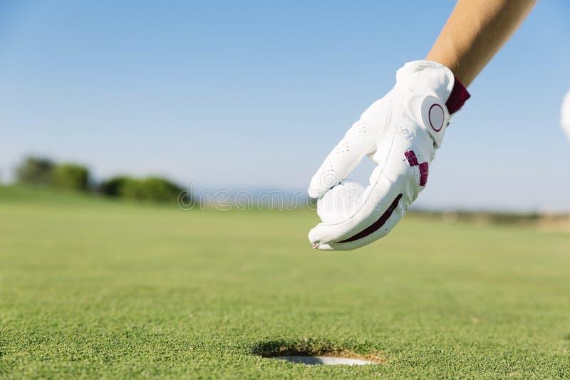 WomanÂs Hand, die einen Golfball in Loch setzt stockbilder