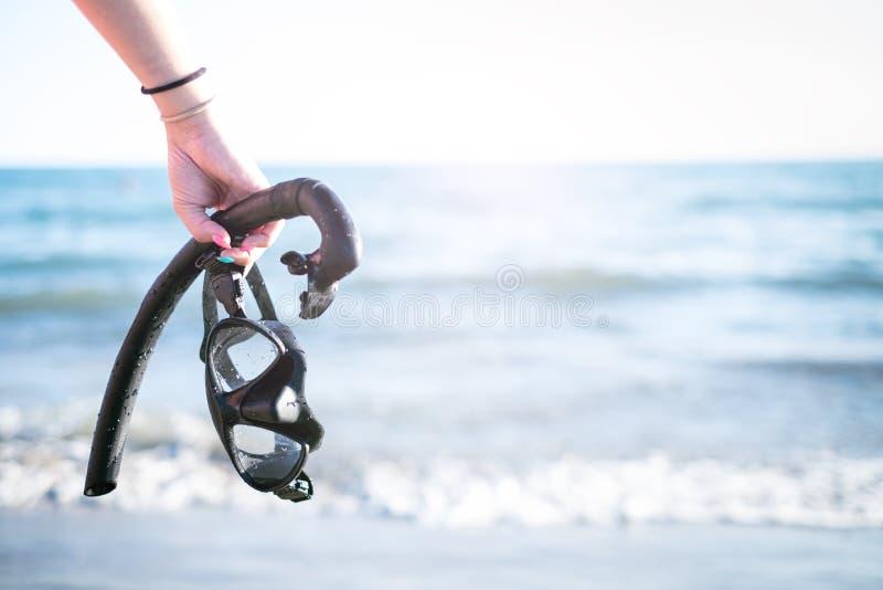 WomanÂs snorkel och maskeringar för handuppehälle på en sandig strand konkurrensar som dyker pölsportar som simmar vatten snorkel arkivbild