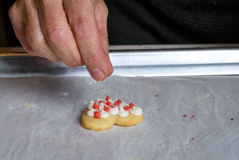 Woman's手落下的糖洒在心形的结霜的糖屑曲奇饼上 库存图片