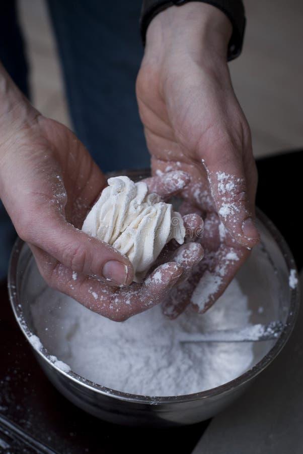 Woman& x27 χέρια του s που ψεκάζουν με τη ζάχαρη τήξης ένα Zephyr Ο ζαχαροπλάστης ψεκάζει την κονιοποιημένη ζάχαρη άσπρο Marshmal στοκ φωτογραφία με δικαίωμα ελεύθερης χρήσης