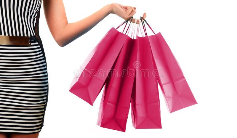 Woman& x27; рука s держа бумажные хозяйственные сумки изолированный на белизне стоковое изображение