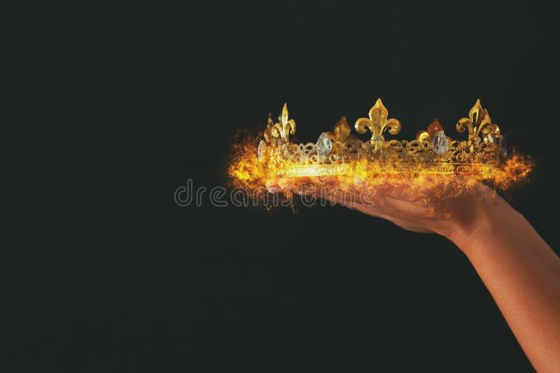 Woman& x27; 拿着在黑背景的s手一个灼烧的冠 免版税库存照片