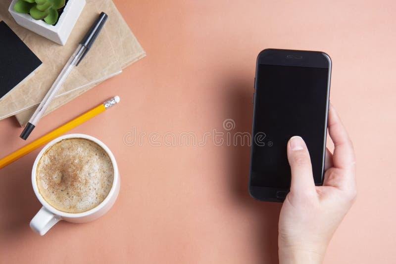 Woman& x27;s手藏品,使用smarphone 职场,工作表witn咖啡杯 顶视图,拷贝空间 新企业的概念 免版税库存图片