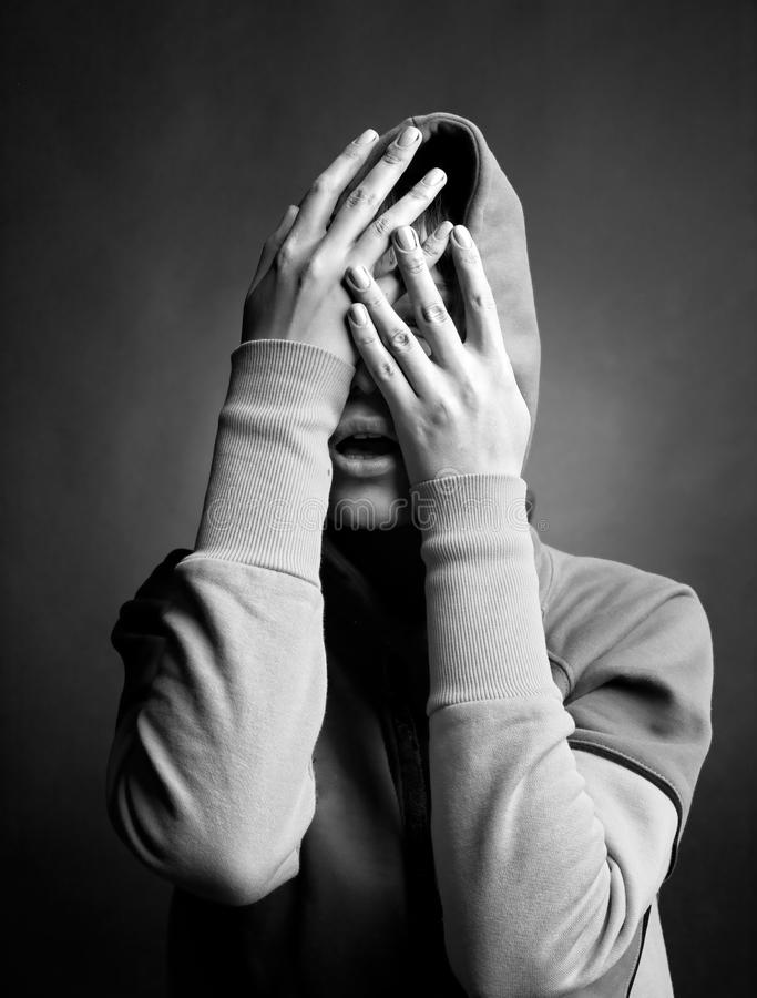 Woman. Young woman hide her face in her hands stock images