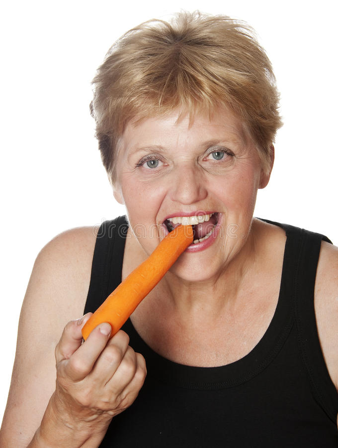 Woman (67 years old) eating a carrots. Health concept royalty free stock images